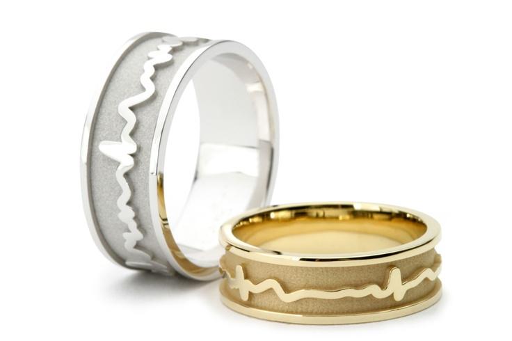 De linker trouwring is uitgevoerd in palladium witgoud en de rechter trouwring in warm geelgoud. De hartslag ligt op de ring en is door een opstaande rand ingekaderd aan twee zijden. De glanzende hartslag en de kaders contrasteren prachtig met de matte verdiepte gedeelten.