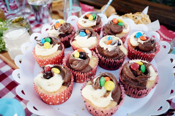 Half chocolate, half vanilla cupcakes topped with icing and M&Ms