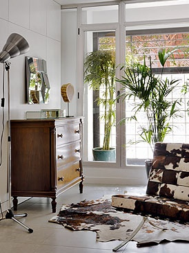 Un sillón Barcelona, de Mies Van der Rohe, en piel de vaca. Está muy bien acompañado por una cómoda clásica y una lámpara de pie, en Ikea