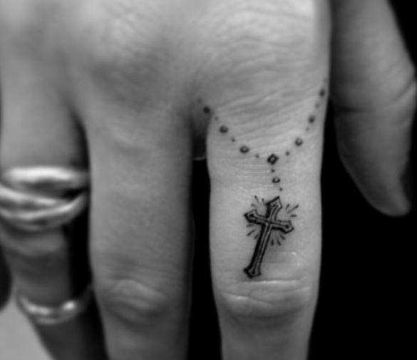 Piccolo tatuaggio croce cristiana sul dito
