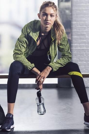 Gigi Hadid wearing Reebok Dance Strappy Bra, Reebok Cardio Leggings, Reebok Studio Reflective Jacket in Hero Yellow and Reebok Hayasu Sneakers