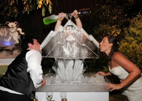 Bride and groom drinking from an ice luge at their wedding reception.