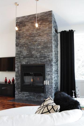 Le manteau de cheminée, habillé de tuiles d'ardoise, trône avec élégance dans l'aire ouverte et réchauffe l'atmosphère de ce séjour au style contemporain, propice à la détente.