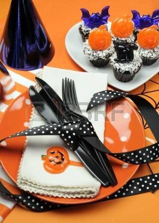 Happy Halloween party tafel met oranje stip platen een chocolade cupcakes met zwarte kat, pompoen en vleermuizen versieringen op oranje achtergrond Verticale photo