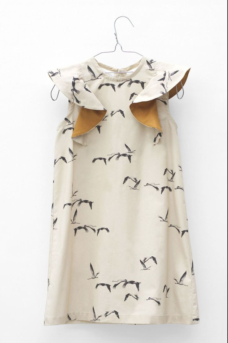 Sleeveless dress in beige & black bird print. Ruffles on shoulders with contrast underside. Zipper closure on back. 100% Cotton. Machine wash up to 30 C. Gentle cycle. Do not bleach. No tumble dry. Ir