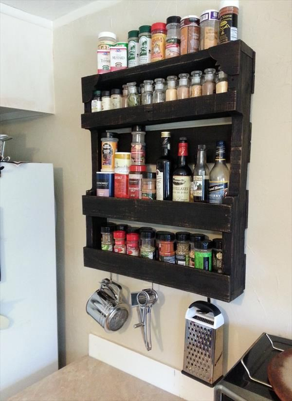 Isn't it amazing that a coat of black paint takes an average pallet from rustic to sleek almost immediately? Even better: This wooden shelving unit features four shelves for spices — not to mention hangers for a cheese grater and more below.