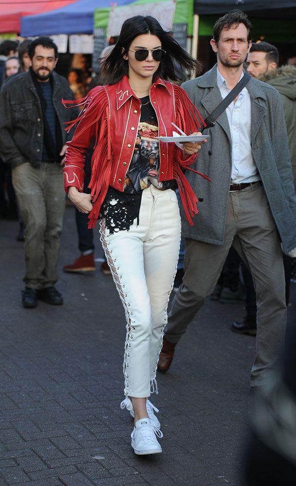 Kendall Jenner usa tendência de calça com amarrações com t-shirt de banda e jaqueta de franjas vermelha