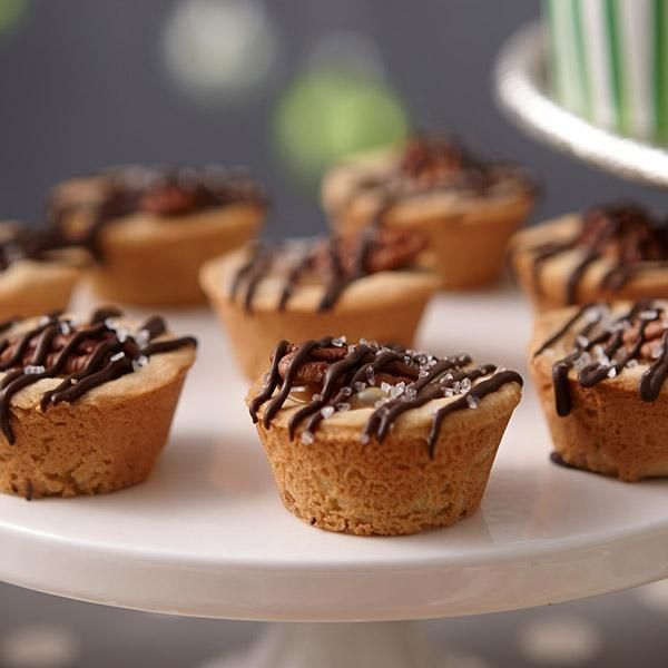 Salted Turtle Cookie Cups - If you're a fan of salty-and-sweet, do we have a cookie for you! Ooey gooey caramel, melted dark cocoa Candy Melts candy and a crunchy pecan top a buttery brown sugar cookie cup. A sprinkling of salt makes it even more divine.