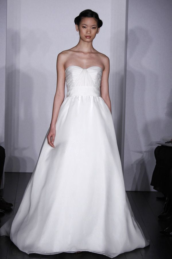 Silk Organza. Strapless full A-line with draped bodice and softly gathered skirt. Grosgrain ribbon accents natural waist. Available in Silk White as sampled.