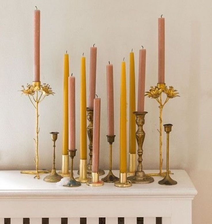 pink and mustard yellow candles with gold stands. / sfgirlbybay