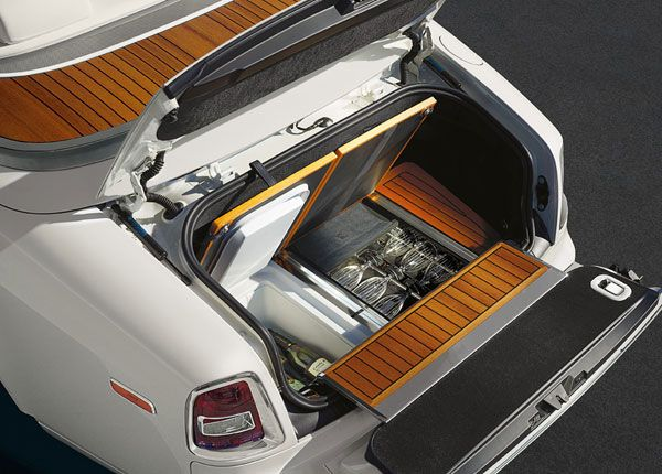 "2013 Rolls Royce Phantom Drophead Coupé… you pop open the trunk and you're greeted by the teak flooring you'd expect on your yacht… which then pops open further to reveal a ""comfortable picnic seat for two adults"" as well as a mini fridge and a set of ""full-sized hand-engraved glasses that were designed by the team at Rolls-Royce"