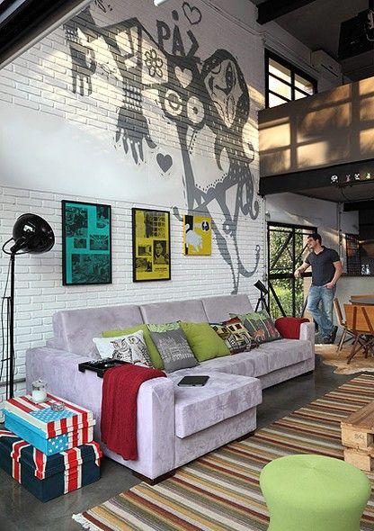 Na sala de estar, o grafite criado por Bruno Dias dá vida à parede branca, harmonizando com os móveis e detalhes coloridos