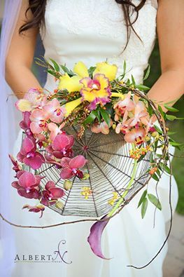 """A Floral Art Piece/Floral Arrangement/Bridal Bouquet Composed Of A """"Spiderweb"""" With A Large Purple Calla Lily, Several Different Species Of Orchid In Pink, Sangria, Yellow & Fuchsia, & Peach + Ivy Type Greenery & Foliage....This Floral Design Is By Artist Albert Ng****"""
