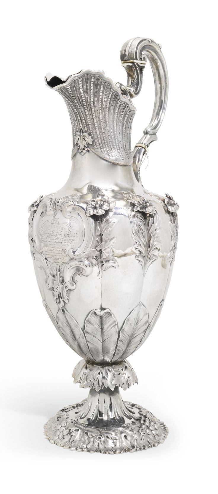 A Victorian silver presentation ewer, Robert W. Smith, Dublin, 1843 the inscribed and crested fluted vase-shaped body chased with foliage and applied with cast flowerheads, hinged lid, the silver handle with ivory fillets