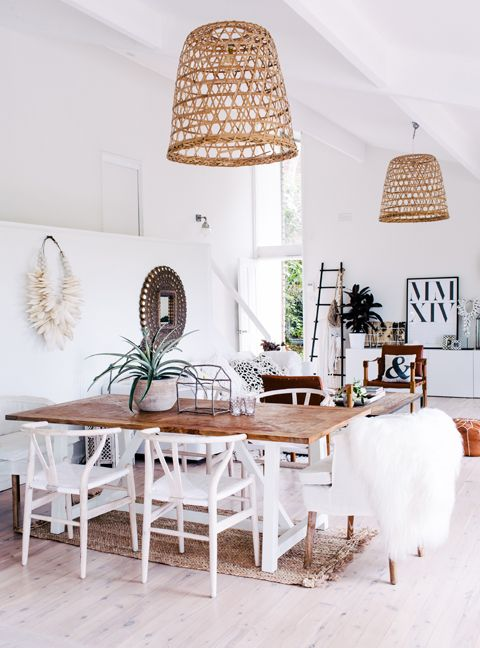light and airy dining room with rustic boho feel. White chairs with farm table and whicker hanging lights