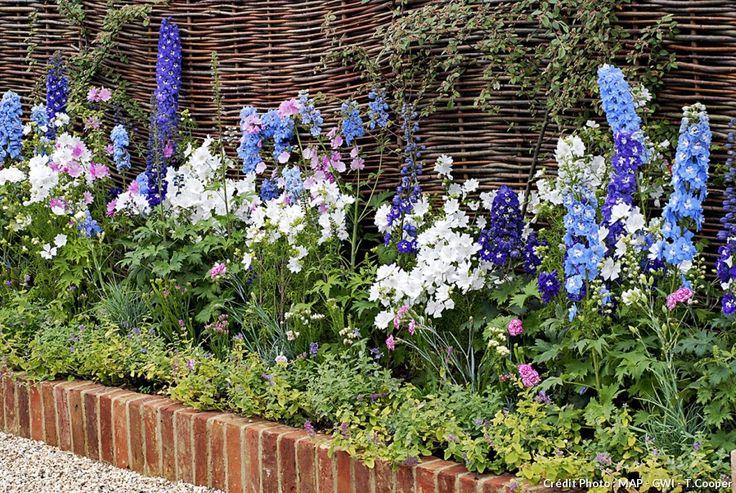 En brique. C'est vrai que les Anglais sont fous de bordures de briques. Mais il n'y a pas qu'eux! Monet, dans son splendide jardin de Giverny, avait bordé ses massifs avec des briques enterrées verticalement de moitié et en biais. Un exemple facile à reproduire et très décoratif.