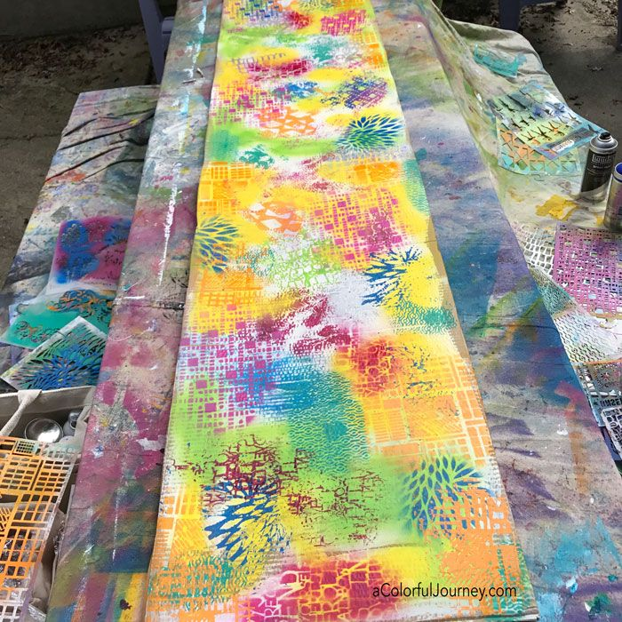 This is what happens when I have a big piece of IKEA cardboard, Liquitex spray paint, and StencilGirl stencils and in the video Carolyn Dube shares how to make a quick mask to prevent oversprays