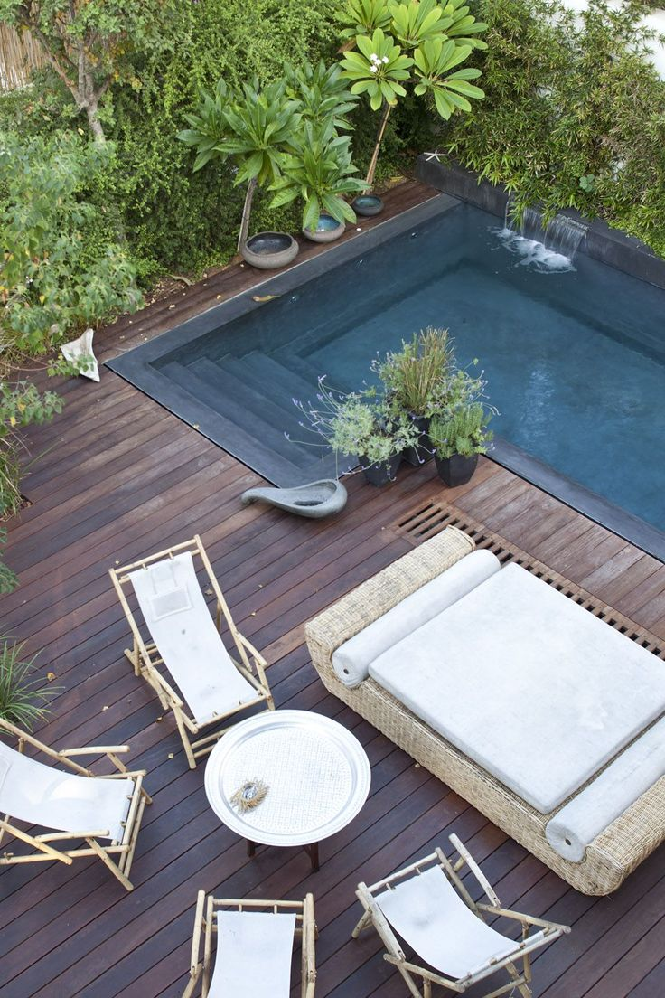 Wooden deck with pool and lush landscaping