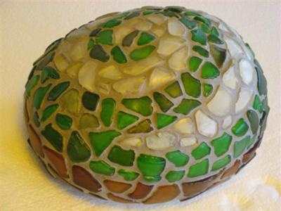 "Beach Glass ""koru"" (spiral)  pattern on rock.The koru design means new life in the Maori language. By Lin Schneider."