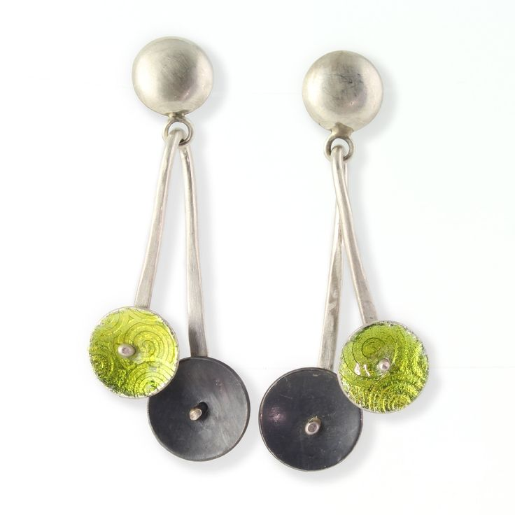 Lime Pendulum Earring by Jennifer Park. This pair of dangle earrings is made of silver and enamel. One disc is oxidized sterling silver and the other a bright shade of lime green. Both are riveted to the hand-forged wire frame. They hang from sterling silver button posts. Clean with mild soap and water. Do not polish oxidized silver.
