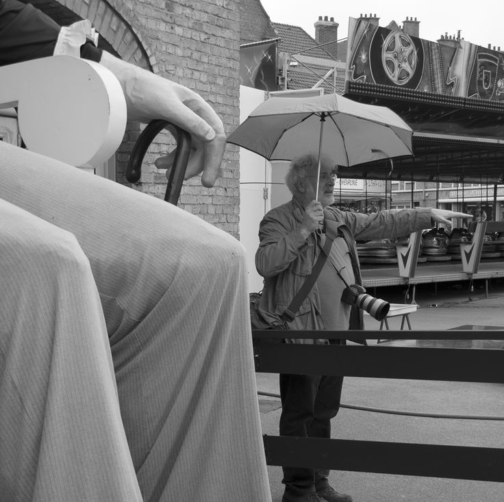 photo noir et blanc montrant un homme parapluie ouvert testant si la pluie tombe alors que le géant à son côtés à un parapluie clos. Cette scène est prise au beffroi de Bergues dans le nord de la France.