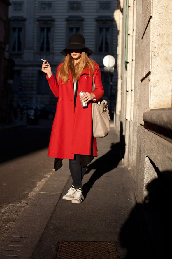 Red coat, black skinnies, white canvas sneakers, black brimmed hat. Photo by The Sartorialist.