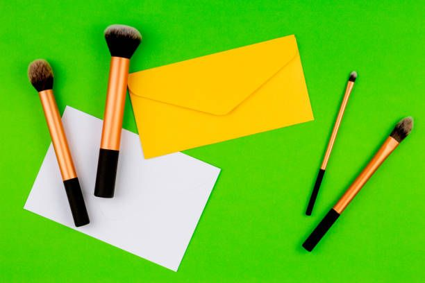 make up brushes with yellow envelope and white blank card on greenery