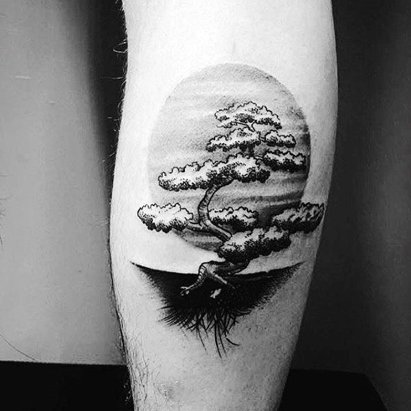 Man With Black Ink Shaded Bonsai Tree And Sun Tattoo On Leg