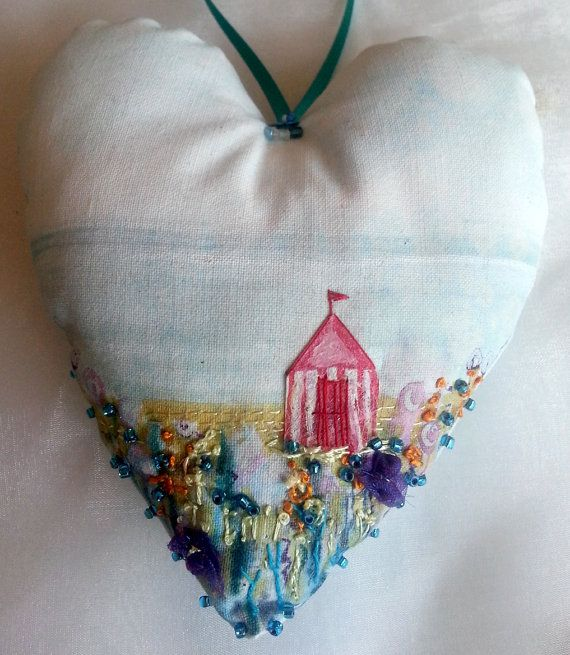 Seaside beach hut painted on hand sewn fabric heart with beads and embroidery, I found this really awesome Etsy listing at https://www.etsy.com/listing/184363750/seaside-embroidered-hanging-heart-with