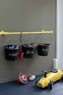 Buckets hanging on curtain rods. Neat and cheap and easy! Love it