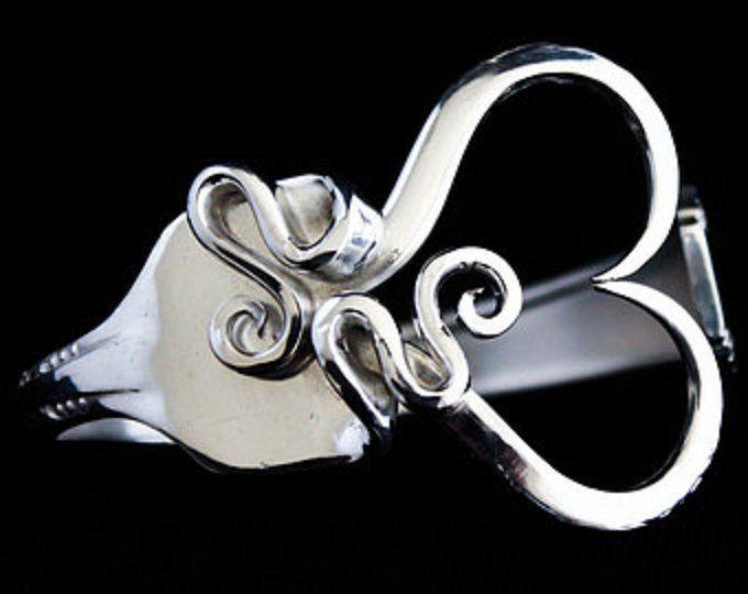 Esta pulsera está hecha de un tenedor de plata antiguo real. El diseño es forjado utilizando sólo herramientas de mano a mano. Se trata de un arte puro de la mano. Es metamórfico en la naturaleza. Las herramientas que utilizo para hacer que estos son hechos mano. Me enseñaron a seguir estrictas reglas de portabilidad al hacer estos. Por lo que su ropa, pelo, piel, amigos y familiares siguen siendo perfectamente seguros en todo momento de dientes de horquillas de rogue.  Esta pulsera está…