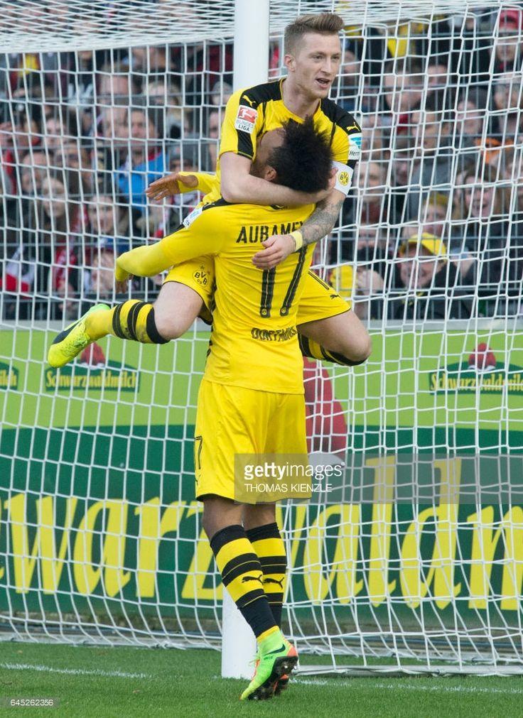Dortmund's Gabonese forward Pierre-Emerick Aubameyang celebrates with Dortmund's forward Marco Reus after Aubameyang scored the first German division Bundesliga football match between SC Freiburg and Borussia Dortmund in Freiburg, southwestern Germany, on February 25, 2017. / AFP / THOMAS