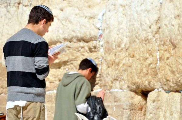 An observant Jewish youth prays at the Western (Wailing) Wall in Jerusalem.  The fringed garment that is showing under his sweater is called a tallit katan (small prayer shawl), which is not mandated in Biblical law, but is stronglymore...