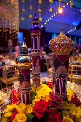 """The handcrafted centerpieces are minature, stylized versions of St. Petersburg's famed """"onion"""" spires and turrets. Three different turrets are on each table, each turret is topped with an inverted Christmas tree ornament and embellished by hand with glitter and jewels. Masses of daffodils, red roses and gloriosas surround the base of the pieces."""