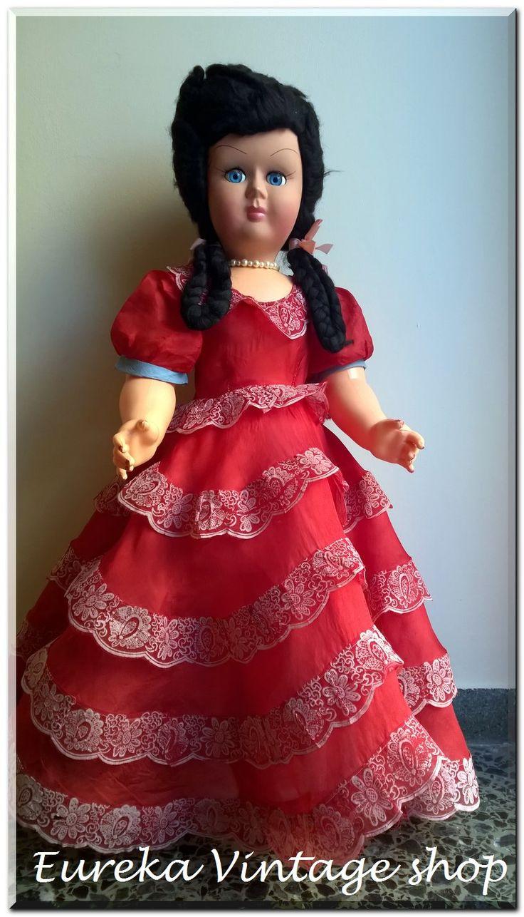 Μεγάλη κούκλα καναπέ από την δεκαετία 1970's.  Φτιαγμένη από πλαστική ύλη, το κεφάλι από βακελίτη.  Το φόρεμα είναι μεγάλο και εντυπωσιακό.  Όλα τα μέρη κινούνται, τα μάτια ανοιγοκλείνουν.  Η κούκλα είναι σε πολύ καλή κατάσταση για την ηλικία της, όπως και το φόρεμα με φυσιολογική παλαιότητα. Φοράει εσώρουχο, φουρό και παπούτσια.