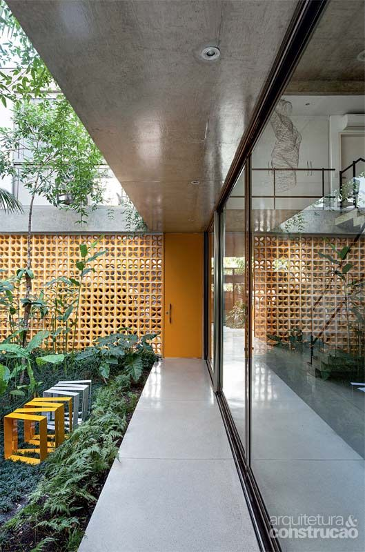 Casa Jardins (Casa 10x38) / CR2 Arquitetura #entry #entrance #door #doorway #wall #hall #corridor #concrete #outdoor #yard #backyard #green #patio #terrace #cobogo #yellow @ElementoV @clarareynaldo