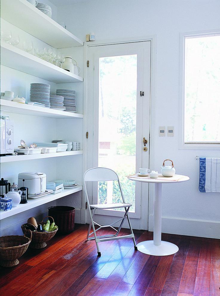 Espacio de almacenamiento abierto y pequeña mesa redonda con silla de hierro, todo pintado de blanco, en la cocina de una casa en Punta del Este, Uruguay.