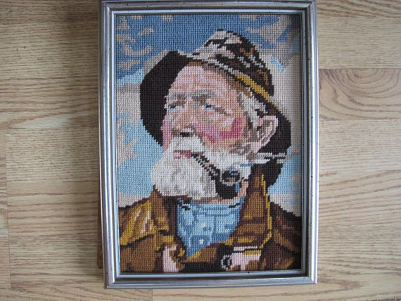 Nicely finished vintage needlepoint picture of a pipe smoking sailor with rosy cheeks. Dated on th back as 1981/82 - made by Grant Cane. Royal Paris canvas made in France. Framed in a speckled silver tone frame. Overall size is about 13 by 9 1/2 inches in size. Note that backing paper