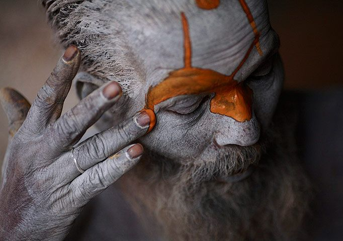 A Hindu sadhu applies paint to his forehead at his ashram at Pashupatinath Temple for the Shivaratri festival. Shivaratri is dedicated to Lord Shiva; holy men mark the occasion by praying, smoking marijuana or smearing their bodies with ashes