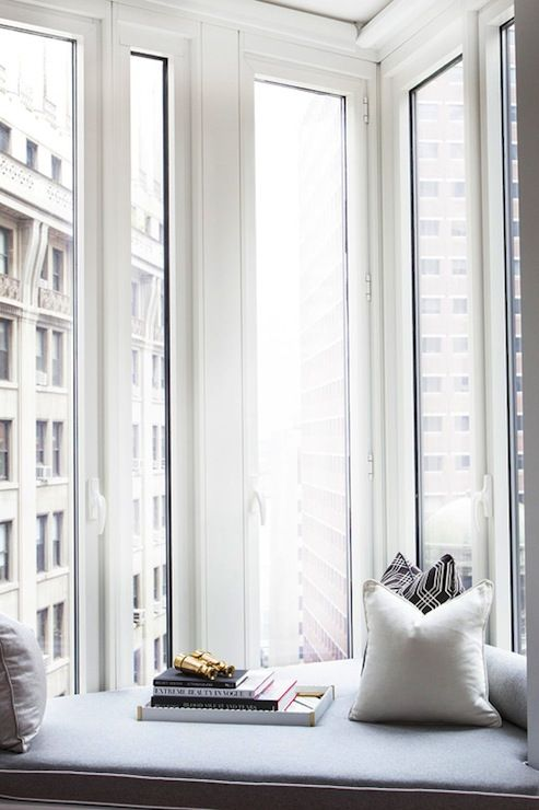 home office with spectacular views of the city :: wall of tall windows and built in window seat with a blue cushion and a collection of solid and patterned pillows