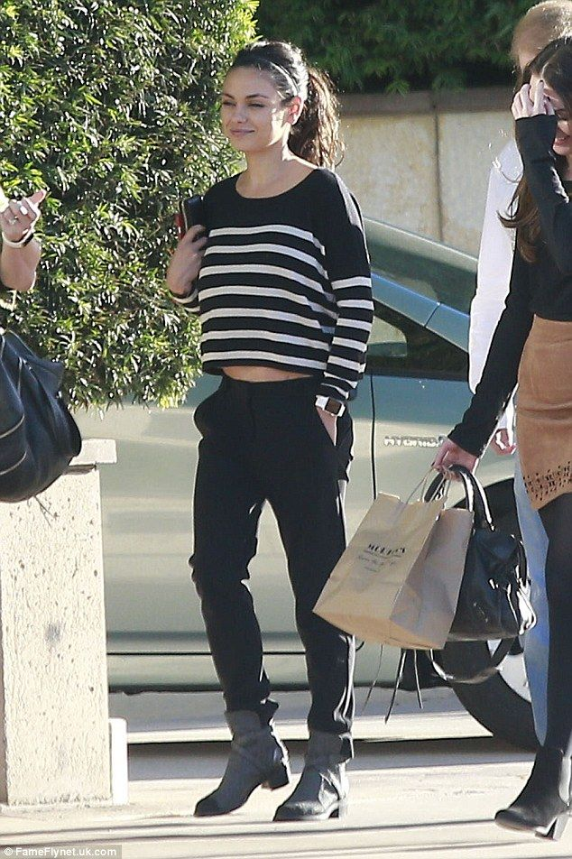Beaming: Mila Kunis looked like a woman with plenty to smile about as she headed out with a friend near her home in Los Angeles on Monday