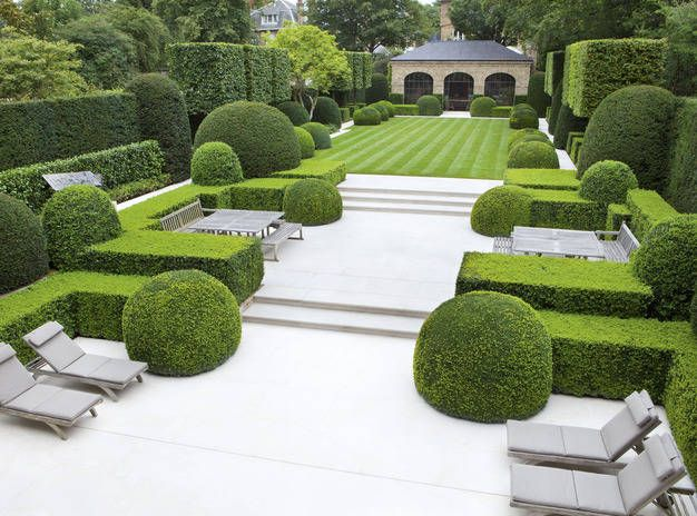 This must be the gardens of an hotel with such a large area of terrace and different places to sit.  Good, well-maintained topiary.