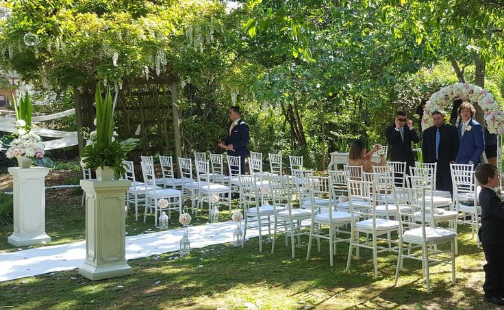 Outdoor wedding ceremony set up featuring tiffany chairs, bridal arch, white carpet, pedestals & florals