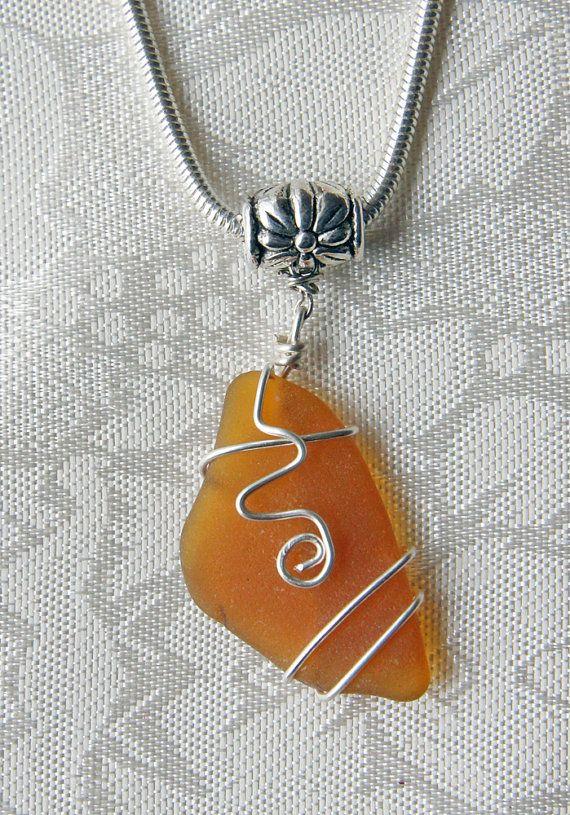 This sea glass pendant consists of a beautifully frosted shard of authentic amber sea glass which has been wire wrapped and further adorned with a wire swirl embellishment. The pendant hangs from a silver metal spacer with a floral design. the spacer fits European style chains, as well as other chains, cords, and ribbon necklaces.    The wide hole beads and the chain necklace shown in one of the photographs are not included with your purchase. They are shown to illustrate how the sea glass…