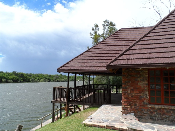View of the river under a cool lightweight  corrosion resistant Woodshake thatch roof