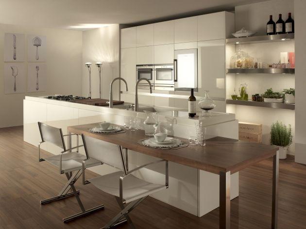Estos muebles de color blanco y de madera marrón son para la cocina. Ya hay todo lo que puede servir en la cocina: horno doble, doble lavabo, lavavajillas, frigorífico, un gran plan para cocinar, estantes de acero que sirven de despensa. La idea de tener una isla en la cocina me gusta mucho. Esta isla se prolonga y se convierte en una mesa con sillas, adecuada para el desayuno.