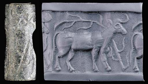 Late Uruk Jemdet Nasr black stone cylinder seal, 3rd millenium B.C.   Deeply engraved with a bull in profile to the right, a plant rising from the ground in front of the animal and bending over its back, 3 cm long. Private collection