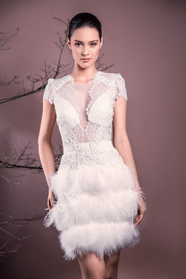 CRISTALLINI SKA574 - A spectacular dress made of Chantilly lace and feathered swan, is a statement of elegance. Angelic feathers emanating story offers an air of femininity and sensuality.  Chantilly French lace, italian tulle 100% polyamide, beads and delicate handmade embroidery, swan feathers, ostrich feathers,crepe lining for added comfort  Partially lined, waistband  Hook and fastenings zip at back, Swarovski button Incorporated push-up bra cups for support  Dry cle...