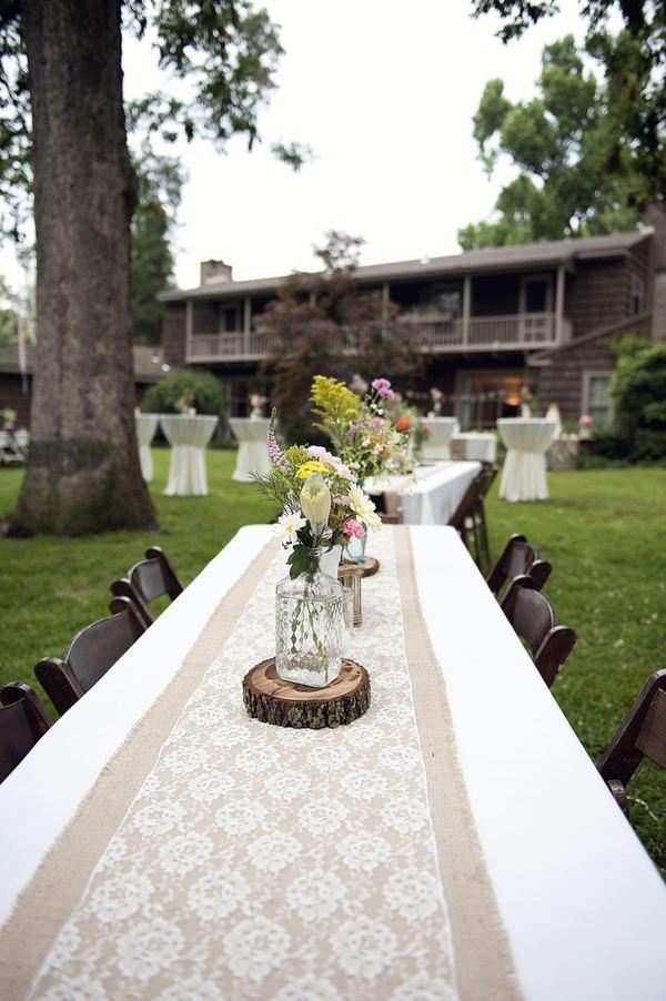 Of toch deze? Jute tafelloper met kant erover en houten boomstam tafelstuk