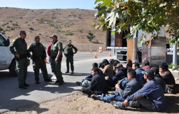 Border patrol agents apprehend a large group of illegal immigrants who attempted to cross the San Diego-Tijuana boundary hidden in a commercial vehicle. This San Ysidro border crossing is the busiest in the world, with over 40 million people entering the United States.